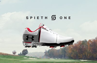 Product shot of white pair of UA Spieth One Golf Shoes in front of a golf course