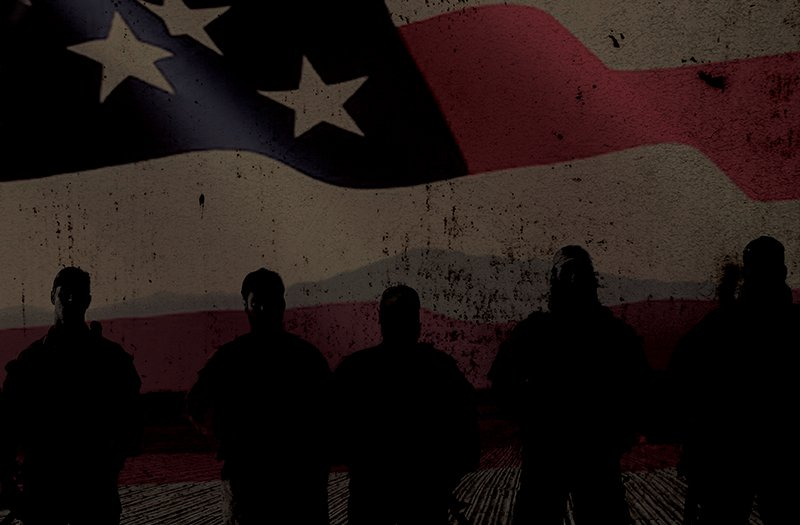 The dark shadows of 5 soldiers standing in front of an American flag graphic.