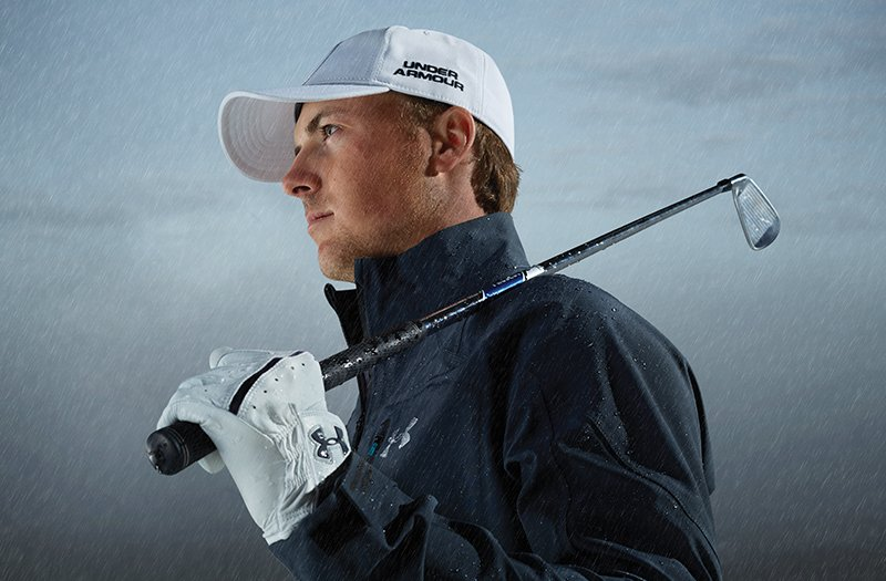 Jordan Spieth in a water-resistant sweatshirt, standing still with a golf club on his shoulder
