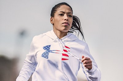 Woman wearing white UA big logo flag hoodie running outside