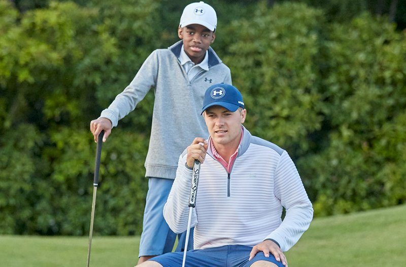 Jordan Spieth in a white 1/4 zip crouching down, couching a young golfer, also wearing a 1/4 zip