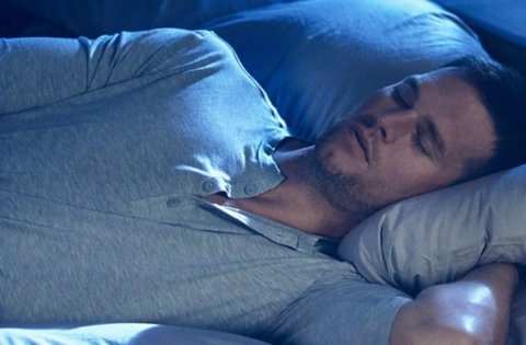 Tom Brady, sleeping peacefully in a bed, wearing TB12 Sleep Recovery sleepwear.