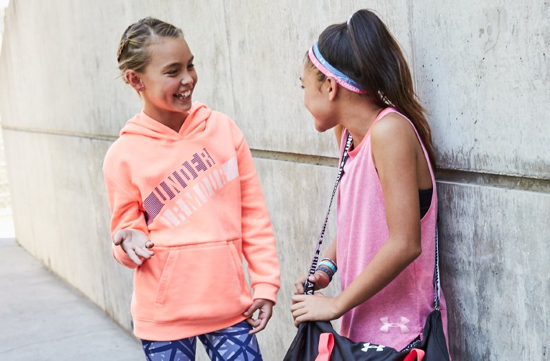 Girls chatting outside school about their favorite gymnastic gifts that they got for Christmas.