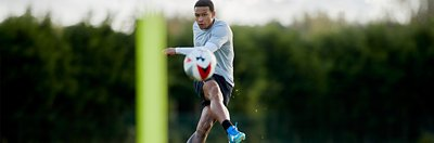 Memphis Depay wearing a grey shirt, black shorts and blue UA soccer cleats running towards a ball