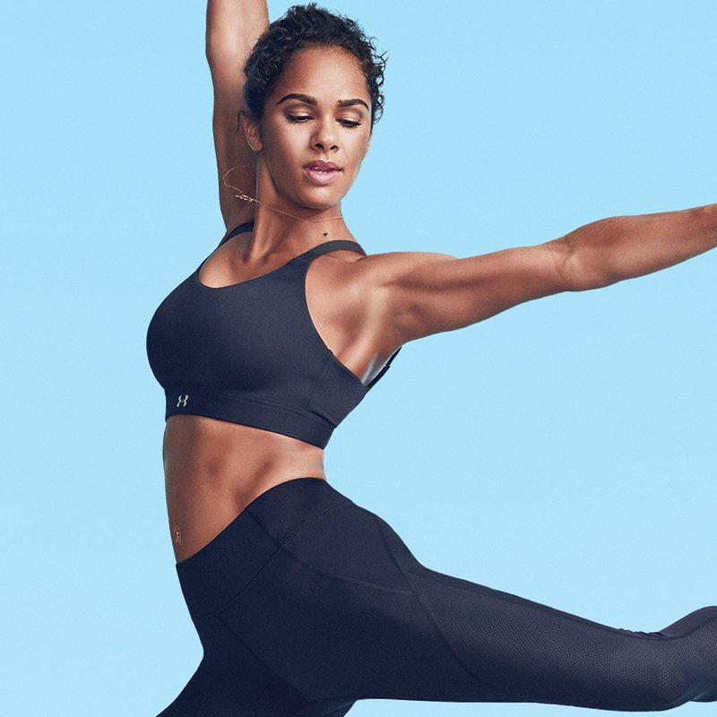 Misty Copeland wearing a black UA Eclipse sports bra and black leggings leaping while dancing.