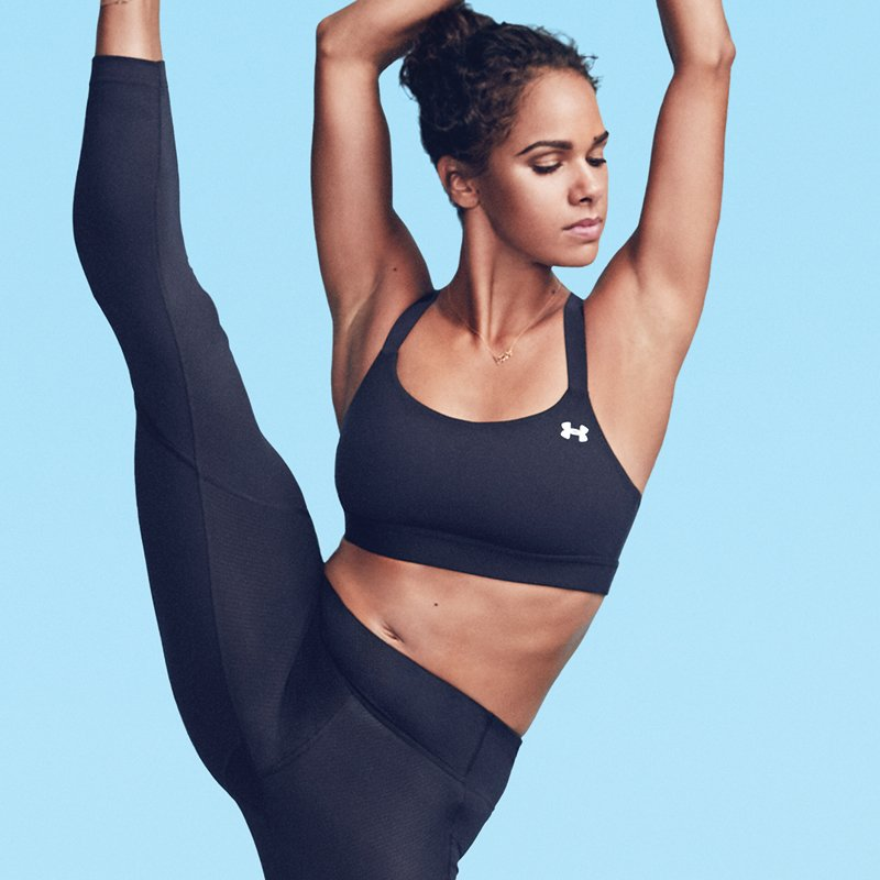 Misty Copeland wearing a black UA Eclipse sports bra and black leggings stretching her leg with a hi