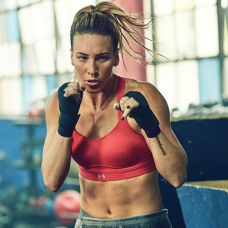 Woman wearing red UA Eclipse sports bra with raised fists boxing in a gym.