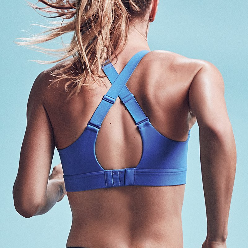 Woman facing backwards wearing blue UA Eclipse sports bra while running.