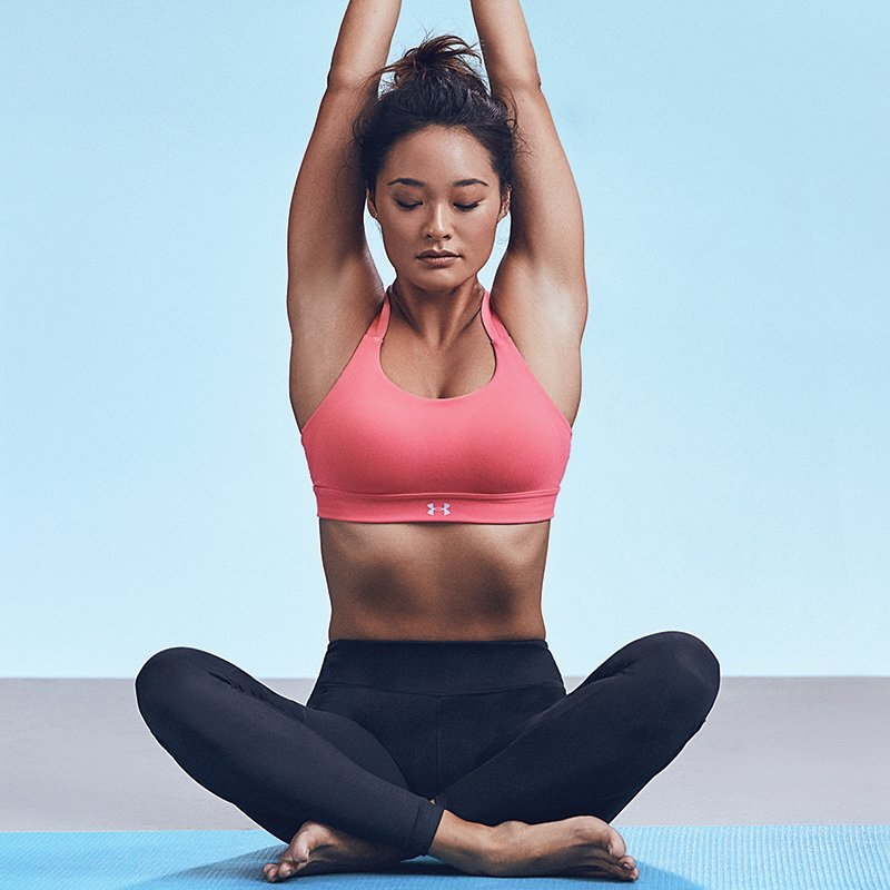 Woman wearing pink UA Eclipse sports bra and black leggings practicing yoga while seated on the floo