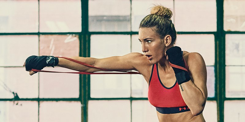 Woman wearing red UA Armour Mid sports bra punching her arm forward with resistance bands.