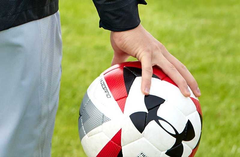 Close up of black, red and white UA soccer ball being held in players hand