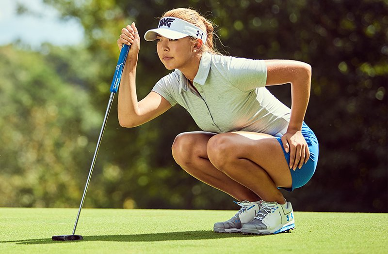 Pro golfer Alison Lee crouching in golf shorts & a polo, on a green golf course