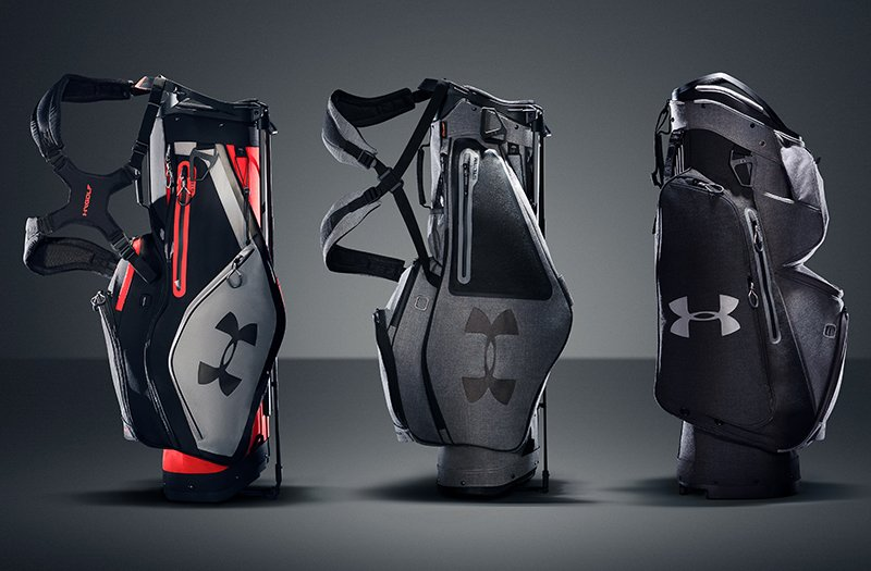 Three black & gray UA golf bags on a stark gray background