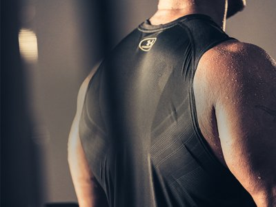 Close up of the back of a guy working out wearing a UA SuperVent training tank with mesh details