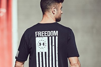 Male facing backwards wearing black UA Freedom T-Shirt featuring a white flag