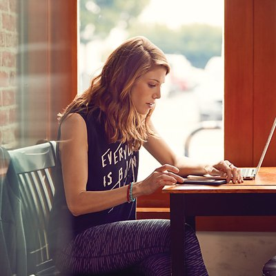 Woman wearing black graphic tank and patterned leggings sitting at a table on her laptop