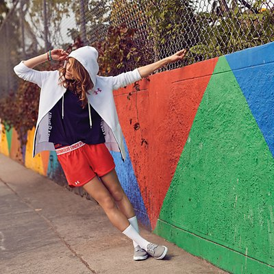 Woman wearing black top, red shorts and white hoodie leaning away from brightly colored wall