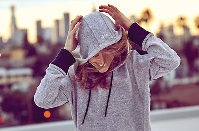 Woman wearing grey UA showstopper hoodie with hood on and hands up on her head