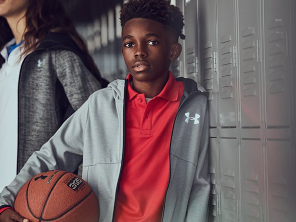 Boy wearing a red UA polo and grey UA jacket holding a UA basketball  leaning up. BOYS  UNIFORMS 2d4716230