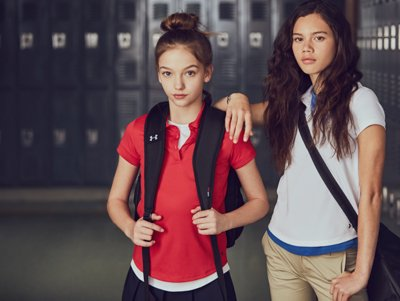 2 girls wearing UA uniform polos, skirt, and pants posing in front of lockers while carrying UA bags