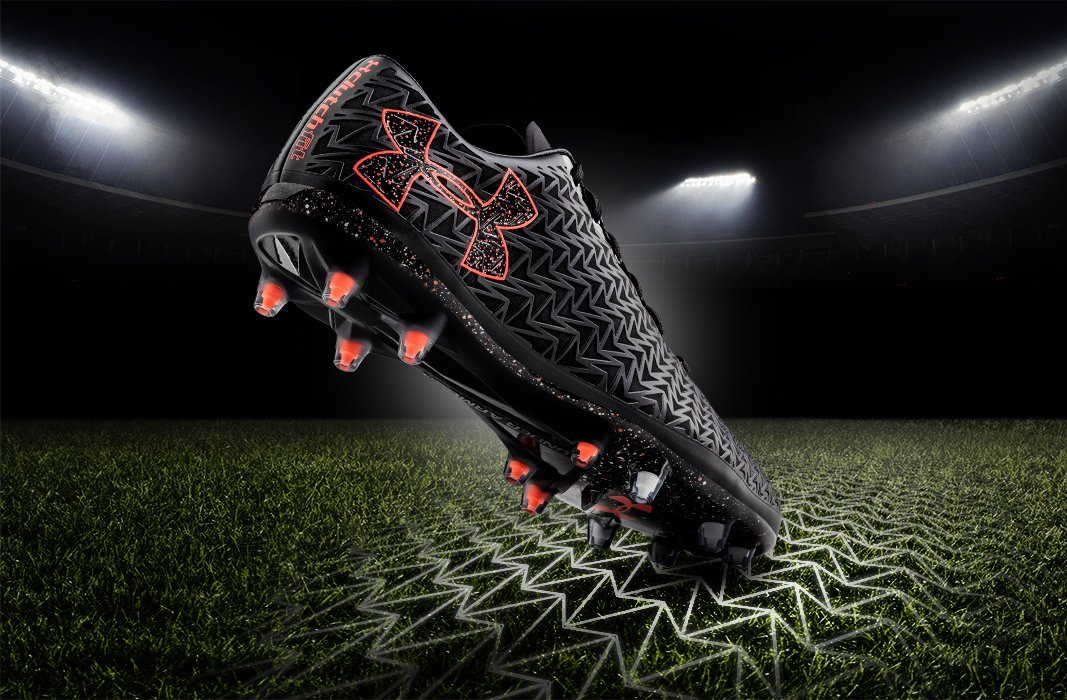 At night, a black and orange UA Clutchfit Force 3.0 Soccer Cleat striking a grass field with the toe