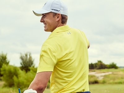 A smiling Jordan Spieth wearing a yellow UA CoolSwitch polo and UA golf hat on a sunny golf course