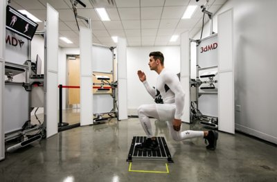Man wearing white UA compression gear holding a lunge position in front of a body scanning machine