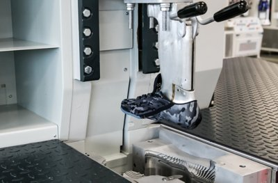 A footwear machine with a black camo UA shoe mold on it being tested in the UA Lighthouse