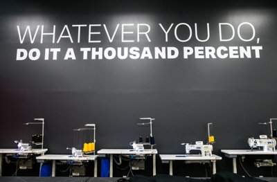Sewing machines lined up in front of a black wall reading whatever you do, do it a thousand percent