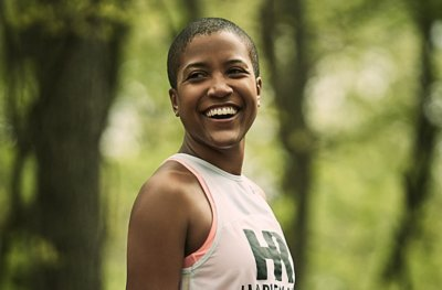 A smiling Alison Desir wearing a white UA tank outside in the woods