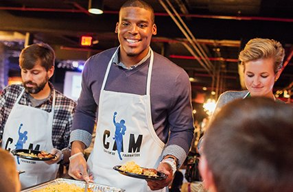 Cam Newton wearing an apron with a big smile on his face serving a meal to a young boy