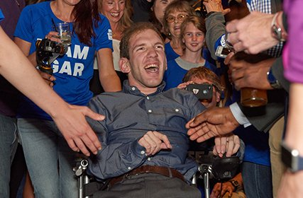 Johnny Agar, a triathlon competitor with cerebral palsy smiling while surrounded by a group of fans