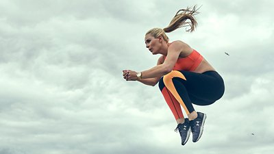 Lindsey Vonn mid air in a tuck jump while wearing orange & black UA leggings & sports bra