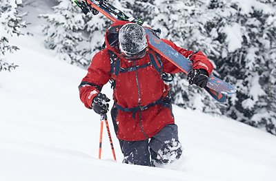 A skier climbing up a snowy mountain with skis over shoulder wearing UA Ski & Snowboard outerwear