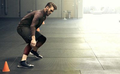 Bryce Harper wearing black & red UA training gear & shoes while practicing speed drills in the gym
