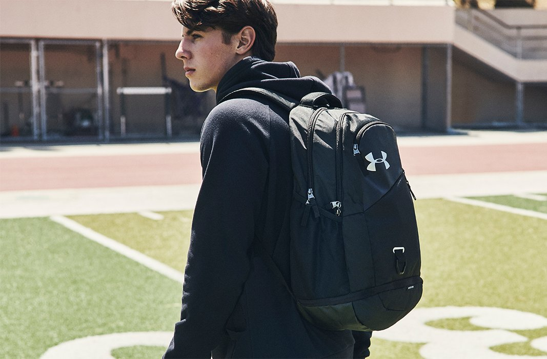 cb5c541e6dae Guy walking across a grass field wearing a black UA hoodie & carrying a  black UA