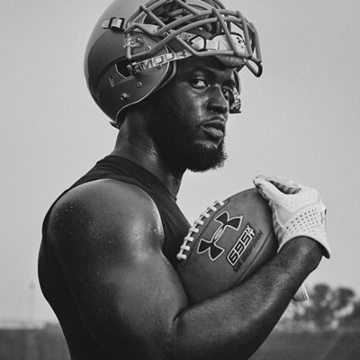 Close-up on Leonard Fournette with helmet on his head holding a football with a white UA football