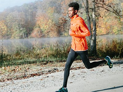 Man running in compression leggings and running jacket by lake in autumn