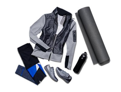 Women's UA studio leggings, jacket, sports bra and shoes from ArmourBox beside a yoga mat